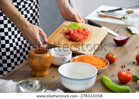 Closeup of chef cook's hands slicing tomato and pepper on a wooden board - stock photo