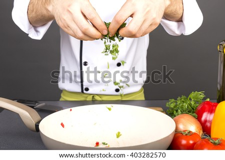 Closeup of chef hands preparing food with organic fresh parsley