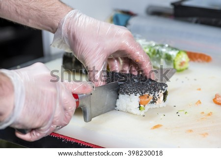 closeup of chef preparing sushi in the kitchen, shallow DOF - stock photo