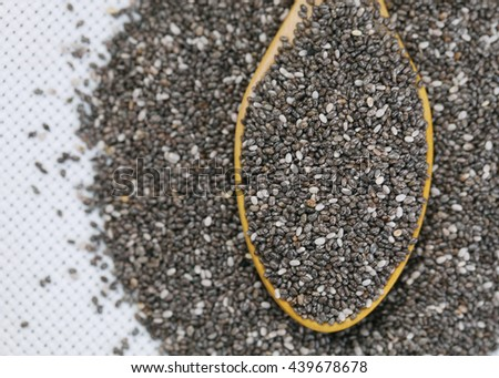 Closeup of Chia seeds in wooden spoon with copy space .View from the top.