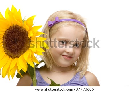 closeup of child (girl) holding a sunflower in hands on white background - stock photo