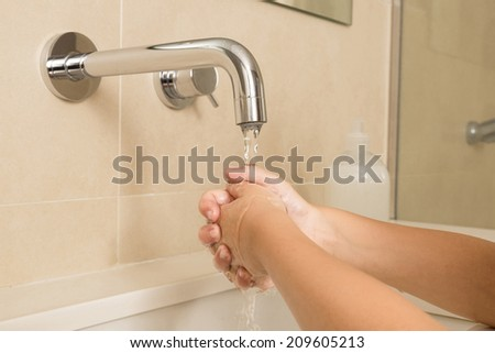 Closeup of child washing hands under the tap