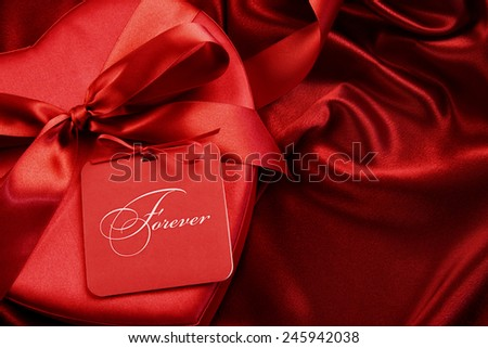 Closeup of chocolate box with gift card on satin background - stock photo