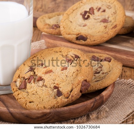 Closeup of chocolate chip cookies and a glass of milk on a wooden plate