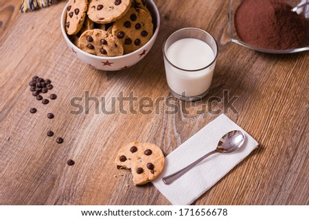 Closeup of chocolate chip cookies on stars bowl and milk glass over a wooden background