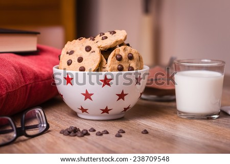 Closeup of chocolate chip cookies on stars bowl and milk glass over a wooden background - stock photo