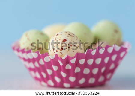 Closeup of chocolate speckled Easter eggs in a crisp sugar shell in cupcape liner. Shallow depth of field.