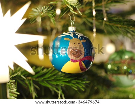 Closeup of christmas ball with a reindeer hanging on decorated christmas tree - stock photo