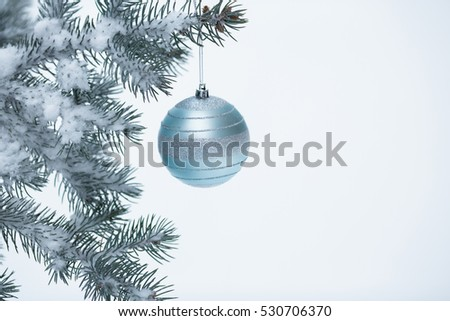 Closeup of Christmas ball with pine branch with snow
