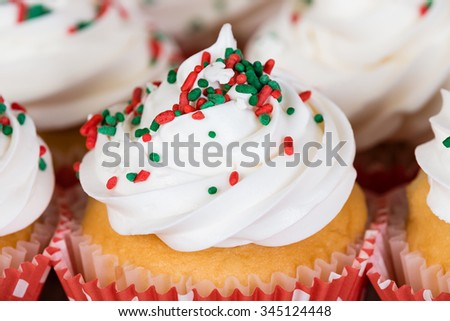Closeup of Christmas cupcake with vanilla frosting and red and green sprinkles - stock photo