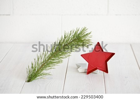 Closeup of Christmas interior decoration in simple, minimalist, elegant style with pine branch on white wood floor and wall background. Plenty of copy space. - stock photo