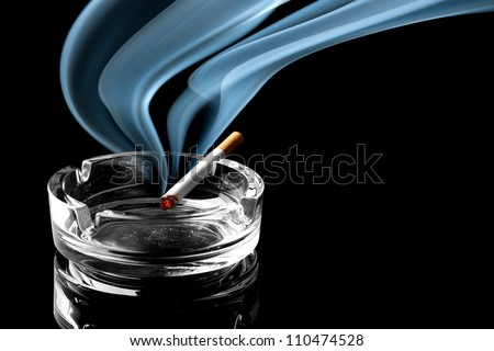 Closeup of cigarette on ashtray with a beautiful wisp of smoke - stock photo