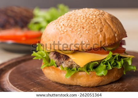 Closeup of classic burger made from beef and fresh vegetables on wooden background - stock photo