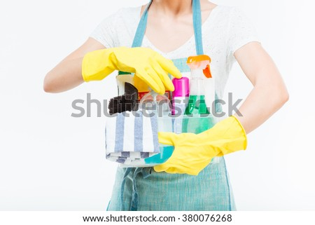 Closeup of cleaning supplies in plactic box holded by young housewife in blue kitchen apron over white background - stock photo