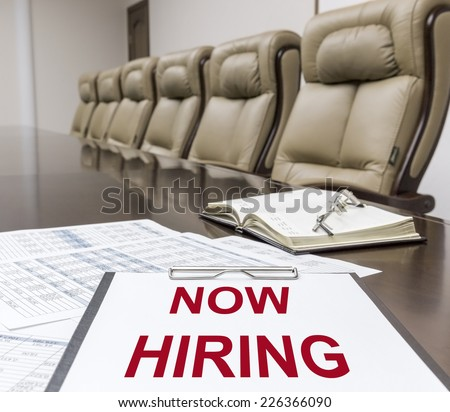 """Closeup of clipboard with """"now hiring"""" text on table in empty corporate conference room before business meeting in office - stock photo"""