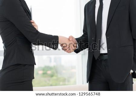 Closeup of co-workers' handshaking - stock photo