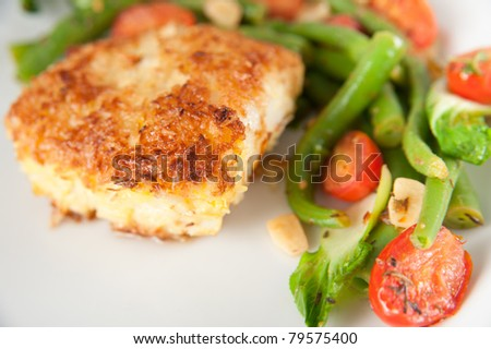 Closeup of Cod Fried  in Coconut Flakes Served with Sauteed Bock Choy, Green Beans and Tomatoes - stock photo