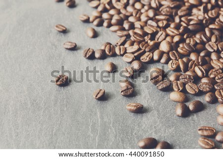 Closeup of coffee beans on grey stone surface. Heap of roasted coffee bean on stone texture with copy space. Coffee shop or cafe background. Natural stone and seeds. Soft color toning - stock photo