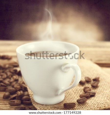 closeup of coffee cup and dark wall background  - stock photo