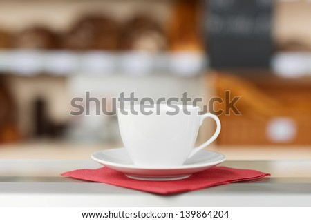 Closeup of coffee cup and saucer on tissue paper