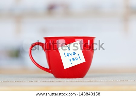 Closeup of coffee cup with I Love You tag on table in kitchen - stock photo