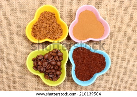 Closeup of coffee grains, ground coffee and granules of instant coffee in colorful glass cups lying on jute canvas - stock photo