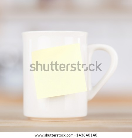 Closeup of coffee mug with blank tag on table in kitchen - stock photo