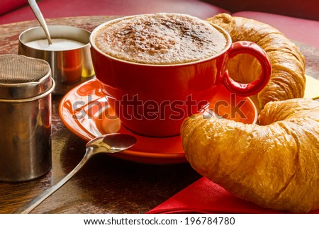 closeup of coffee with frothed milk, cocoa and croissants - stock photo