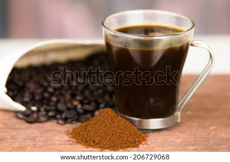 closeup of cofffe cup powder coffee and coffee beans on wooden table selective focus - stock photo