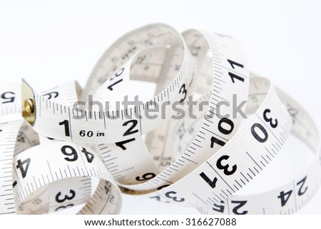 Closeup of coiled measuring tape - stock photo
