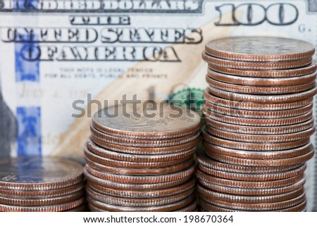 Closeup of coin stacks with hundred dollar bill - stock photo