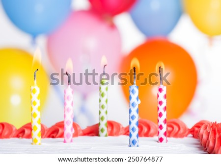 Closeup of colorful birthday candles on a cake with balloons in background