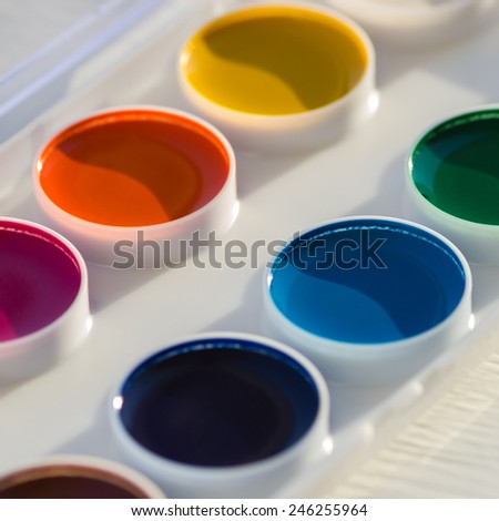 Closeup of colorful new watercolor paint pan set, selective focus on the top of blue paint pan - stock photo