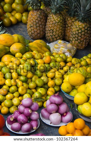 Closeup of colorful pineapple, lemons, limes, oranges & onions in outdoor market