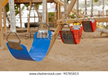 Closeup of colorful plastic swings in a childrens play area at park - stock photo