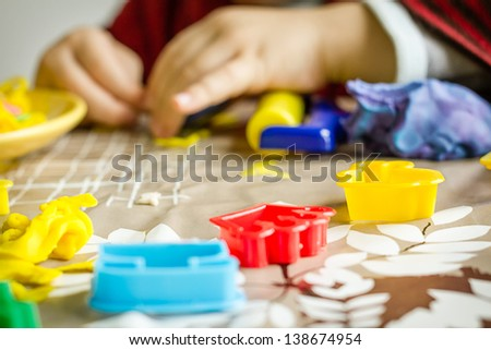 Closeup of colorful plasticine molds and child hands playing on the background - stock photo