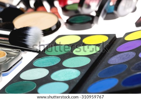 Closeup of colorful set of professional palette of eyeshadow red orange green violet pink yellow purple black beige brown colors powder and make-up brushes on white background, horizontal picture