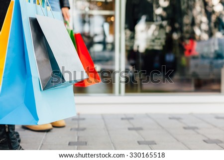 Closeup of colorful shopping bags in front of shopping windows - stock photo