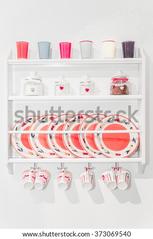 Closeup of Colourful Plates and Dinnerware in a Cupboard on White Wall. Container Seasoning on Shelf. Items Include, Plates, Coffee Plastic and Ceramic Glasses, Tea Pot, and Water Cups. Modern Design. - stock photo