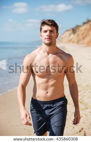 Closeup of confident shirtless young man walking along the beach - stock photo