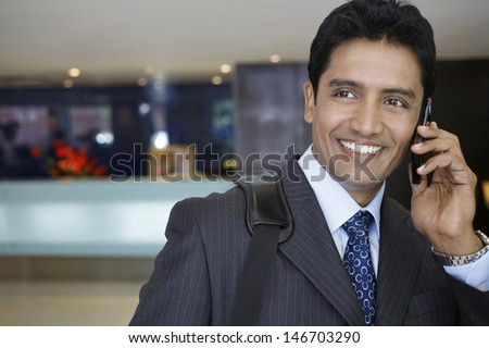 Closeup of confident young businessman using cell phone in hotel lobby - stock photo