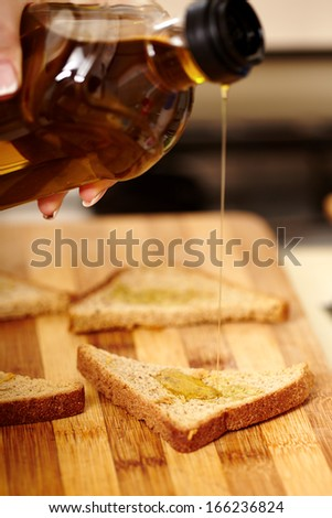Closeup of cook's hand holding a bottle of olive oil and pouring it over finely sliced toasted bread. The making of bruschettas, selective focus