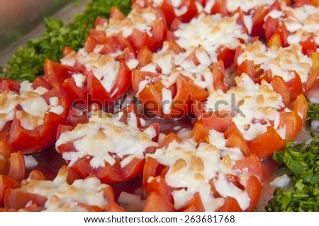 Closeup of cooked tomatoes with melted cheese on display at a hotel restaurant buffet - stock photo