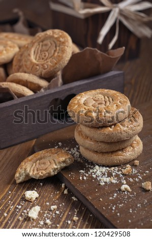Closeup of cookies in the box and dry roses on wooden board. Biscuits stack and one broken cookie with crumbs on cutting board. - stock photo