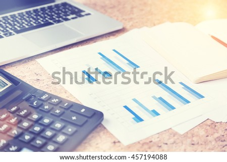Closeup of cork table with keyboard, calculator, business report and blank copybook with pen. Toned image