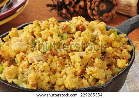 Closeup of cornbread stuffing with chunks of turkey in a cast iron skillet - stock photo