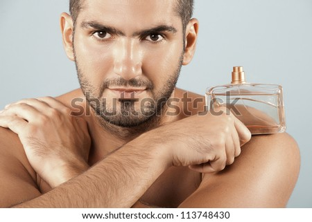 Closeup of cosmetics, Spa young man Holding fragrance. Horizontal, Isolated over Blue background. Studio shot. - stock photo