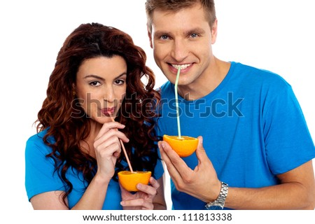 Closeup of couple cuddling and sipping orange juice. Smiling at camera - stock photo