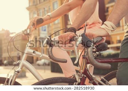 Closeup of couple hands on bikes - stock photo