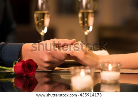 Closeup of couple hands on restaurant table with two glasses of champagne. Romantic couple holding each other's hand at dinner in a luxury restaurant. Marriage proposal and engagement concept.